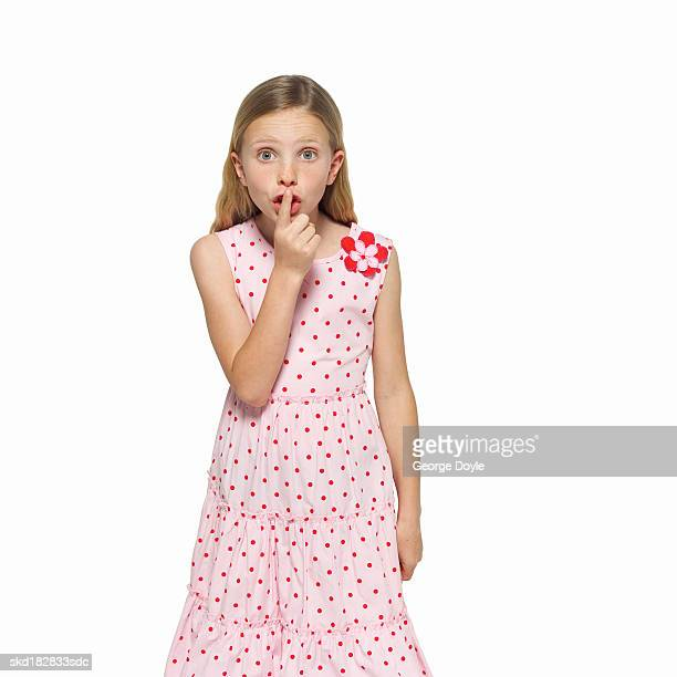 front view portrait of a girl (11-12) gesturing to be quiet with her finger to her mouth