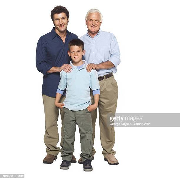 Front view portrait of a grandfather and father and son (10-11) standing