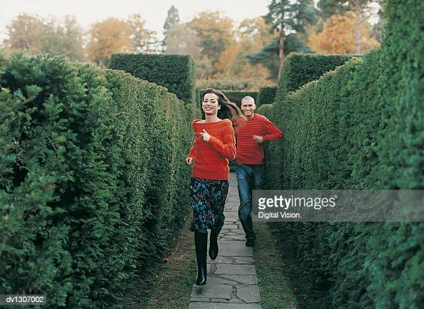 Front View Portrait of a Smiling Young Woman Running in a Maze Chased By a Young Man