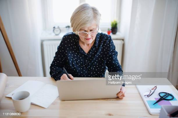 A front view portrait of active senior woman with laptop working in home office.