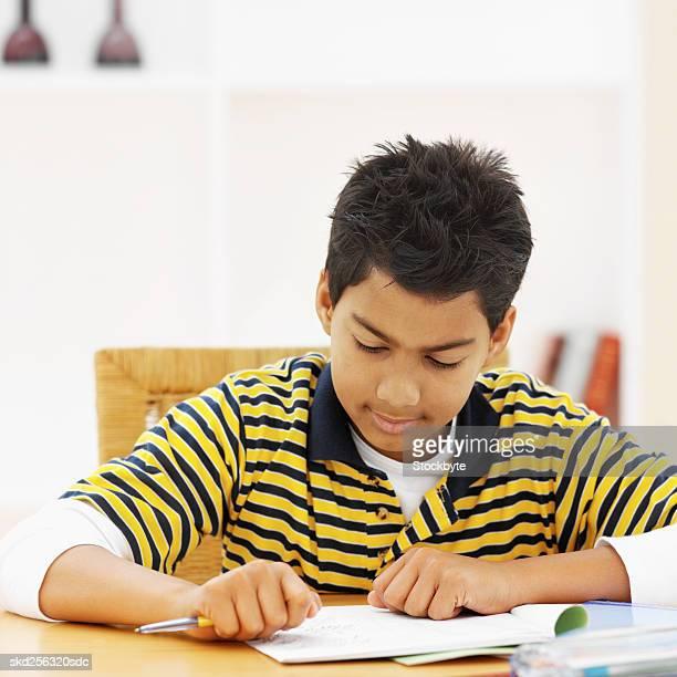 Front view portrait of boy doing homework (11-12)