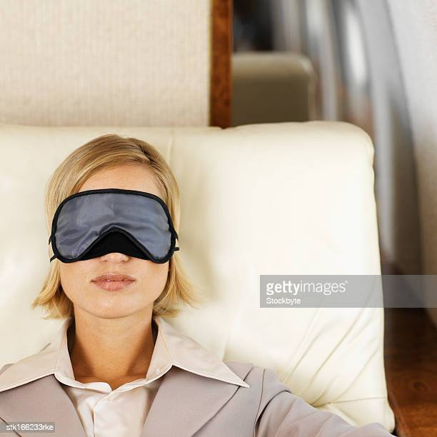 front view portrait of businesswoman sleeping wearing eye mask