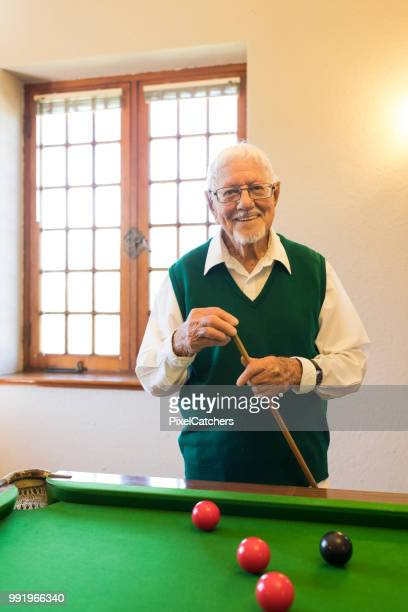 front view portrait of cheerful retired senior man playing pool - old men playing pool stock pictures, royalty-free photos & images
