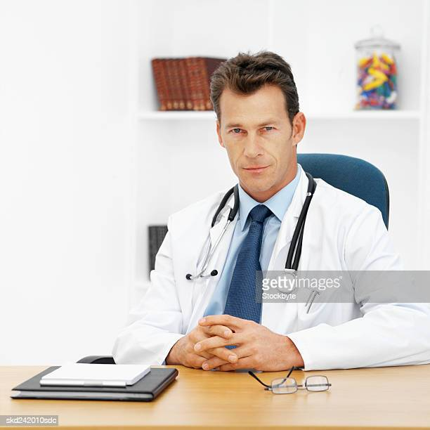 Front view portrait of doctor sitting at desk