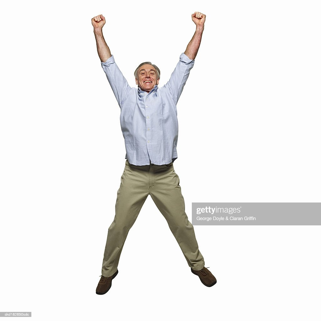 Front view portrait of mature man jumping into the air with arms raised : Stock Photo