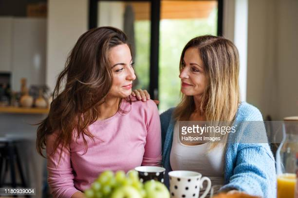 front view portrait of mature mother with adult daughter sitting at home, talking. - alleen vrouwen stockfoto's en -beelden