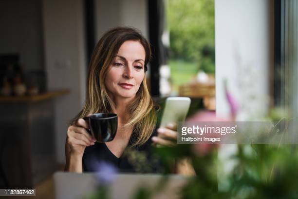 front view portrait of mature woman with laptop sitting indoors at the table, using smartphone. - females stock pictures, royalty-free photos & images