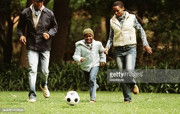 front view portrait of parents and son playing soccer (10-11) - mama futbol fotografías e imágenes de stock