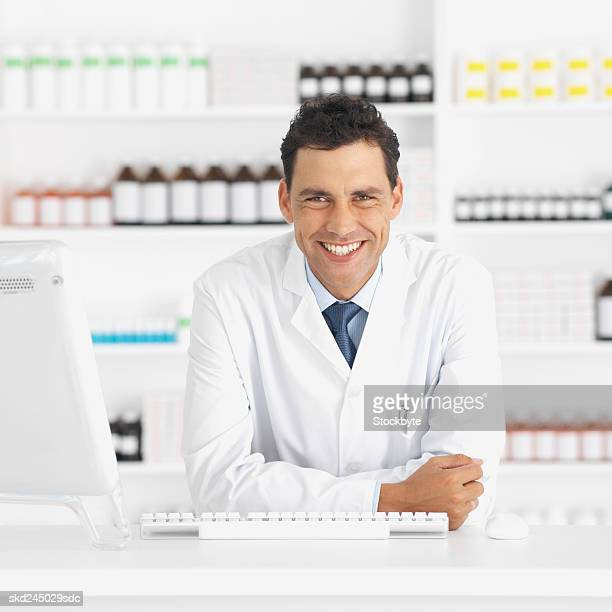 Front view portrait of pharmacist standing at counter