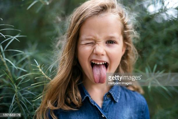 front view portrait of small girl standing outdoors, sticking out tongue. - jungen stock-fotos und bilder