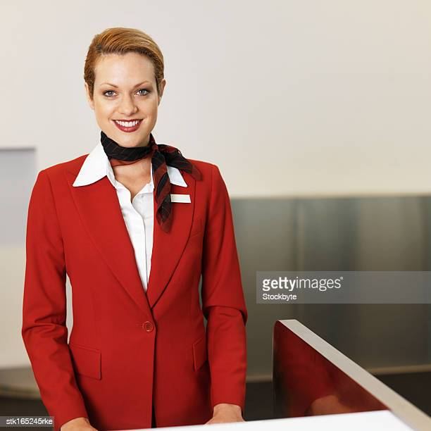 front view portrait of stewardess standing at desk