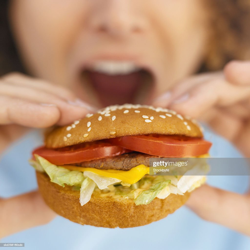 Front view portrait of young man eating burger : Stock Photo