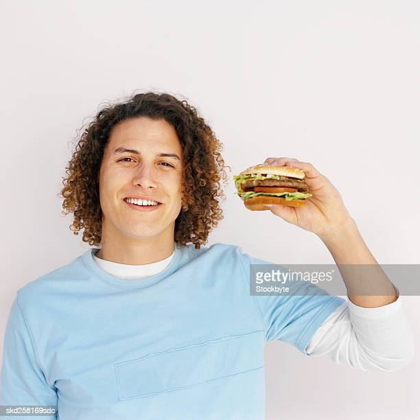 Front view portrait of young man holding burger
