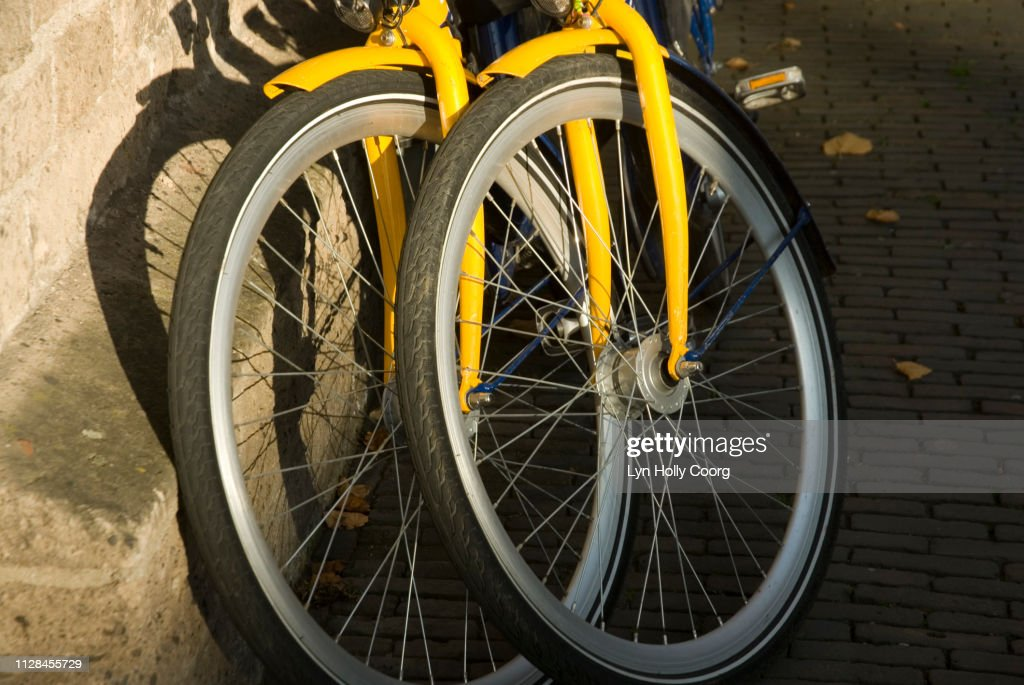 Front wheels of two yellow bicycles propped against wall : Stock Photo