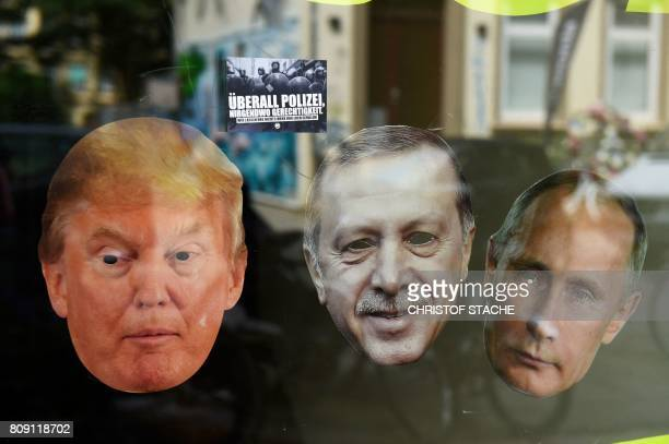 A front window of a house bears the portraits of US President Donald Trump Turkey's President Recep Tayyip Erdogan and Russia's President Vladimir...