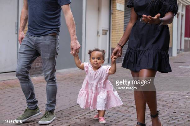 frontal view of a family walking their young daughter - color blindness - fotografias e filmes do acervo