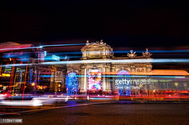 frontal view of alcala gate ('puerta de alcala') at night - madrid stock pictures, royalty-free photos & images