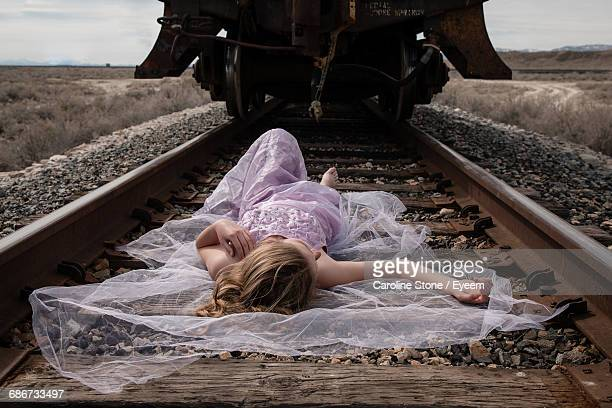 Frontal View Of Woman Lying On A Railway Track