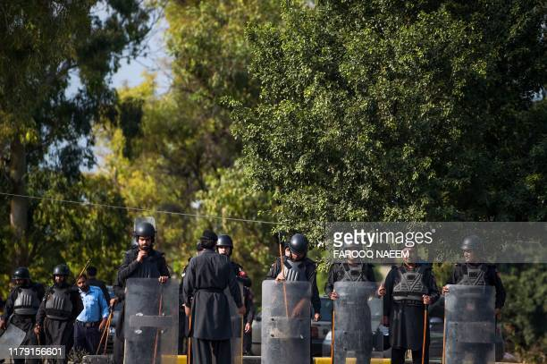 """Frontier Constabulary security personnel stand guard on a road, during an anti-government """"Azadi March"""" led by Jamiat Ulema-e-Islam Chief Maulana..."""