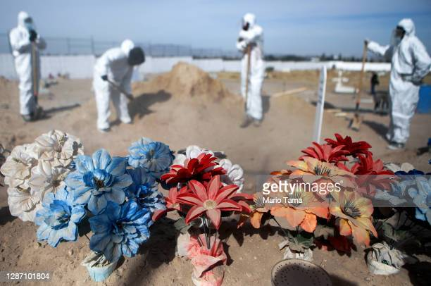 Frontline cemetery workers in full PPE stand by as they bury a victim of COVID-19 at Sueños Eternos cemetery on November 21, 2020 in Ciudad Juarez,...