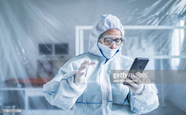 frontline worker trying to connect with his family while is in isolation during covid-19 - frontline worker stock pictures, royalty-free photos & images