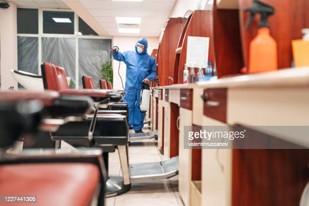 frontline worker with protective suit disinfecting hairdressing studio with chemicals during covid-19 pandemic - world health organisation stock pictures, royalty-free photos & images