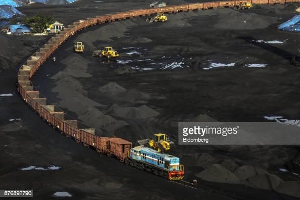 Frontloaders arrange stacks of coal as a freight train sits on rail tracks at Krishnapatnam Port in Krishnapatnam Andhra Pradesh India on Saturday...
