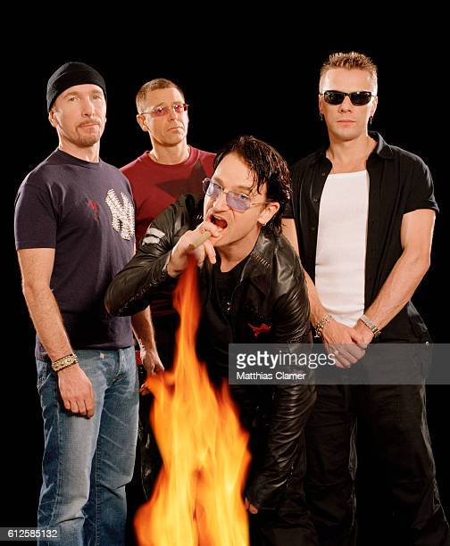 U2 frontman Bono lights his cigar from a large flame as bandmates The Edge Adam Clayton and Larry Mullen Jr stand behind him
