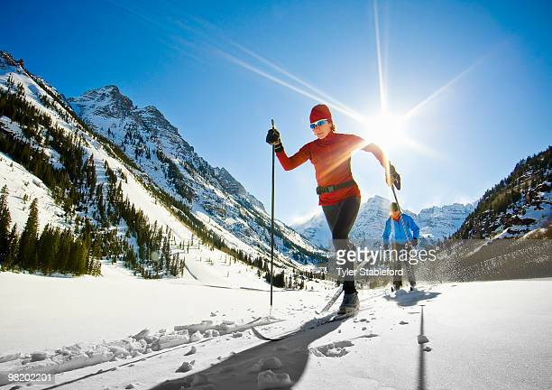 front-view of two female nordic skiers skiing. - colorado stock pictures, royalty-free photos & images