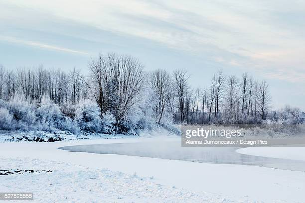 Frost and fresh snow cover the landscape and trees and the river is completely frozen with steam rising in the morning sun