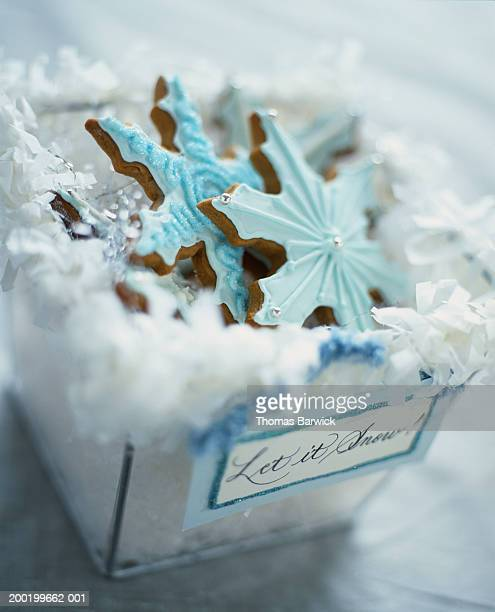 Frosted and decorated snowflake-shaped cookies in box