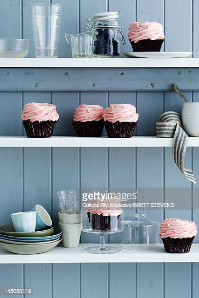 Frosted cupcakes on kitchen shelves