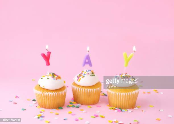 Frosted cupcakes with sprinkles and candles on pink background with confetti.
