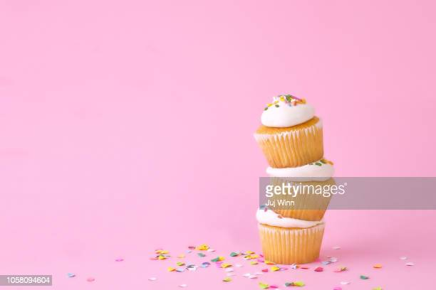 frosted cupcakes with sprinkles and candles on pink background with confetti. - cupcake fotografías e imágenes de stock
