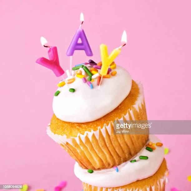 frosted cupcakes with sprinkles and candles on pink background with confetti. - happy birthday stock pictures, royalty-free photos & images