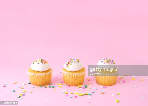 frosted cupcakes with sprinkles on pink background with confetti. - pastel stock pictures, royalty-free photos & images