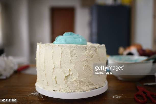 Frosting a blue and white layered cake on a kitchen counter