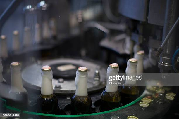 Froth runs down capped bottles of Heineken lager as they pass along a conveyor at the Heineken NV brewery in Den Bosch Netherlands on Tuesday Nov 19...