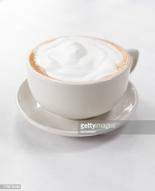 A frothy cappuccino in a white coffee cup