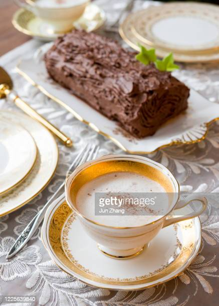 frothy coffee in gantique bone china cup in front of yule log cake - antique stock pictures, royalty-free photos & images