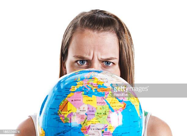 Frowning frustrated young woman holding geographical globe