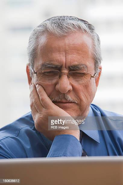 Frowning Hispanic businessman using laptop