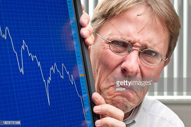 frowning man and sinking stock exchange rate on monitor - distressed stock market people stock pictures, royalty-free photos & images