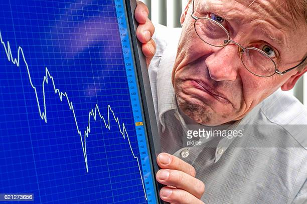 frowning man and sinking stock exchange rate on monitor