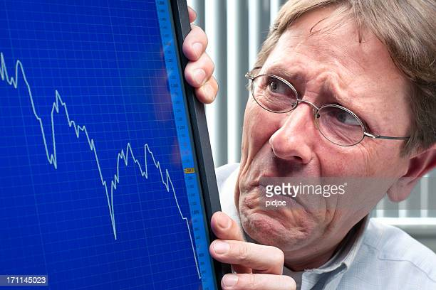 frowning man looking at stock exchange rate xxxl - distressed stock market people stock pictures, royalty-free photos & images