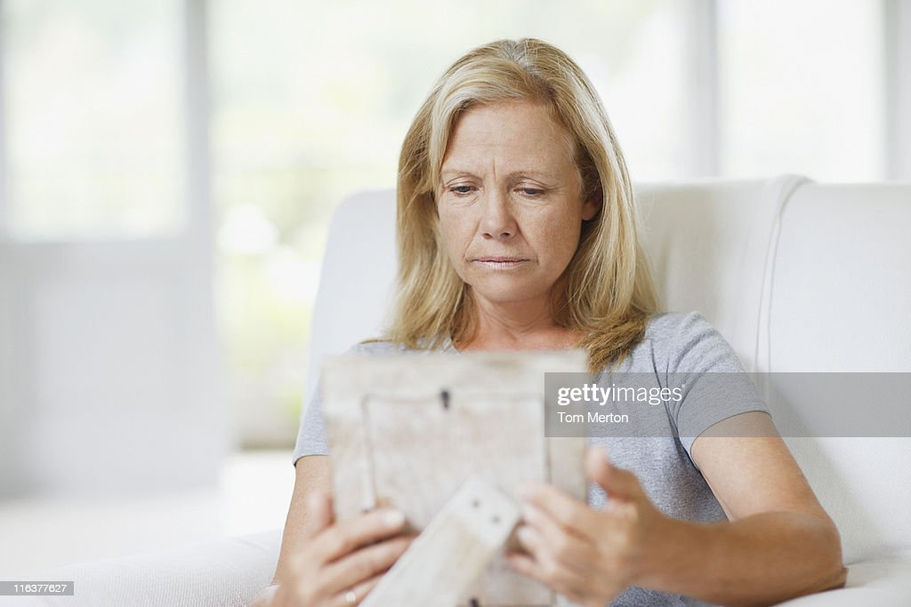 Frowning woman looking at picture frame : Stock Photo