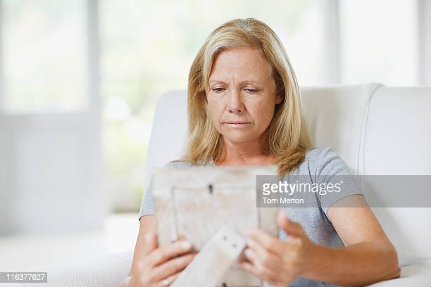frowning woman looking at picture frame - jaded pictures stock pictures, royalty-free photos & images