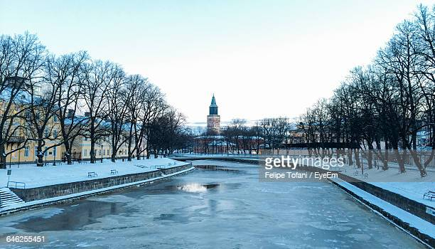 frozen aura river amidst bare trees against clear sky - turku finland stock photos and pictures