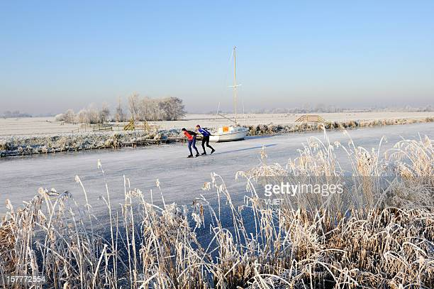 Frozen canal with two ice-skaters