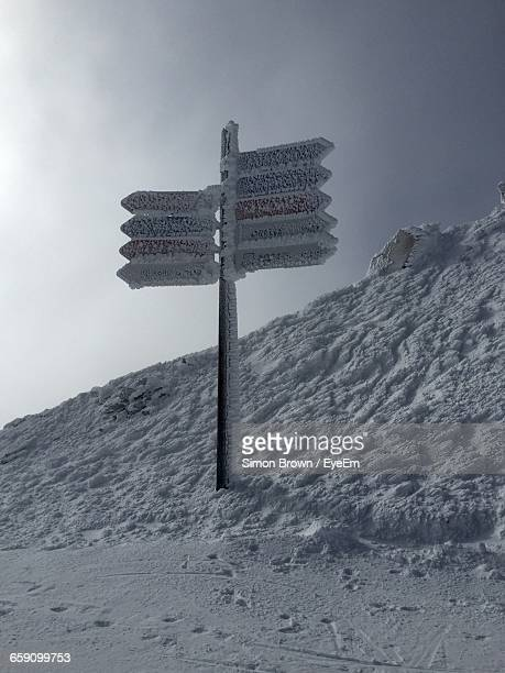 Frozen Directional Signs On Snow Covered Field Against Clear Sky